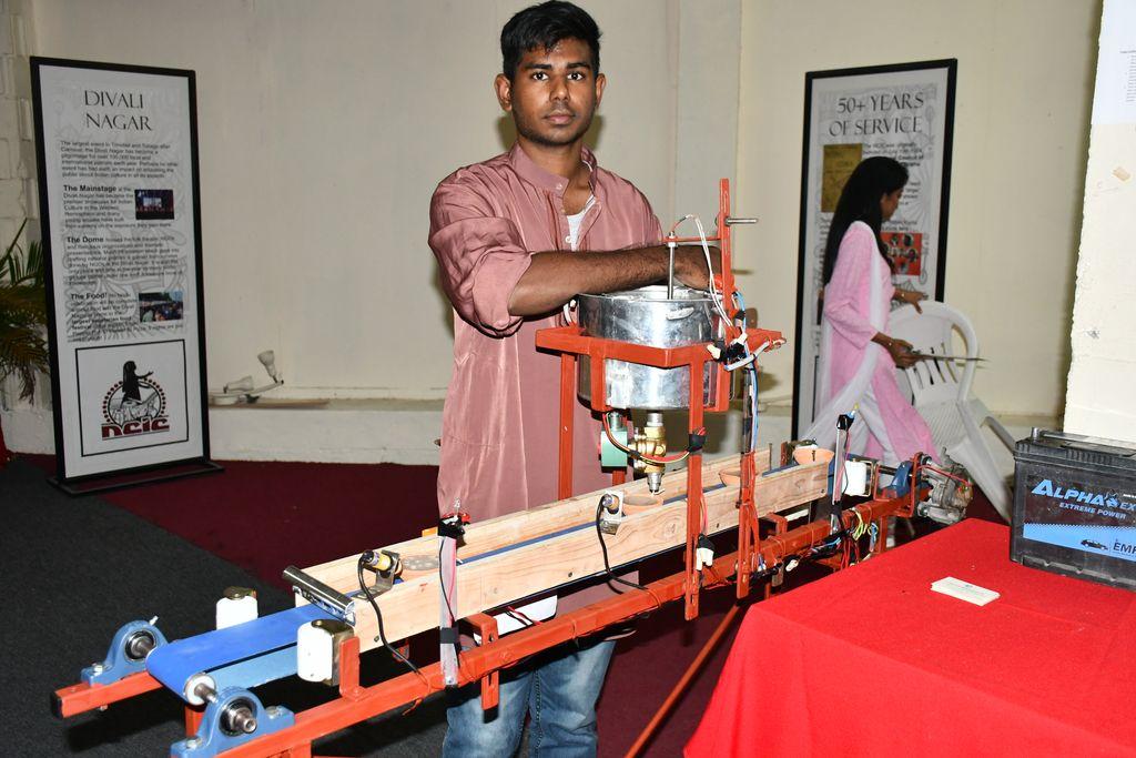 Vikash Brijmohan gives a demonstration of his automated deya filling device at the Divali Nagar on Friday.